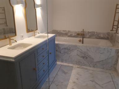 Badkamer getegeld met carrara marmer, geschuurd messing kranen en gecombineerd met stucwerk