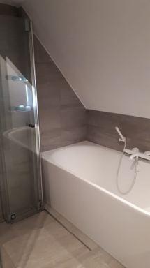 Half vrijstaand bad onder schuin dak met witte kranen