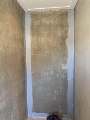 Werken in tijden van het Corona virus. De douchewand voorbereid op het tegelwerk. De wanden staan strak en de naden zijn dichtgezet met kimband en kimpasta voor waterdichte aansluitvoegen.
