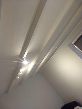 Dakisolatie met minimaal verlaagd plafond om de oude balken te accentueren.