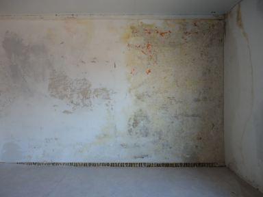pleisterwerk van een slaapkamermuur in Ternat in slechte staat.