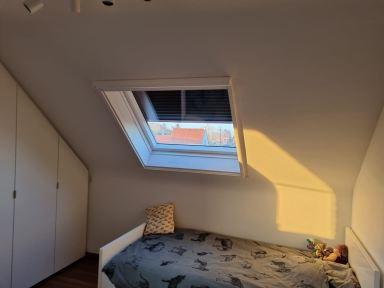 Velux raam plaatsen in Opwijk; kamer één na de werken: raam met rolluik en insectengaas