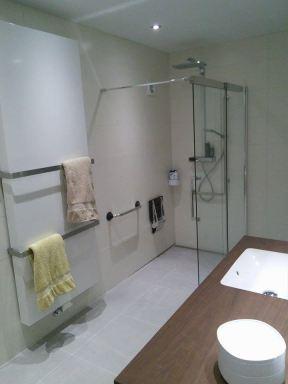 De douchewand kan worden ingeschoven om de doorgang groot genoeg te maken voor een rolstoel.