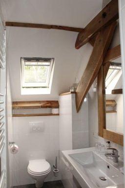 Op veel plaatsen in getracht om de oude balken in het zicht te houden. Ook hier in de badkamer waar tevens een douche , wastafel en hangend toilet zijn geplaatst. Grote witte tegels tegen de wand, antraciet tegels op de vloer afgewisseld met stuc werk en