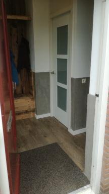 combinatie van beton look met sloophout en hoge plinten geven een mooie uitstraling naast de design deur te  Nuenen
