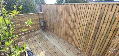 Dakterras met nieuw hekwerk met bamboe en nieuwe vlonderplanken in Dordrecht